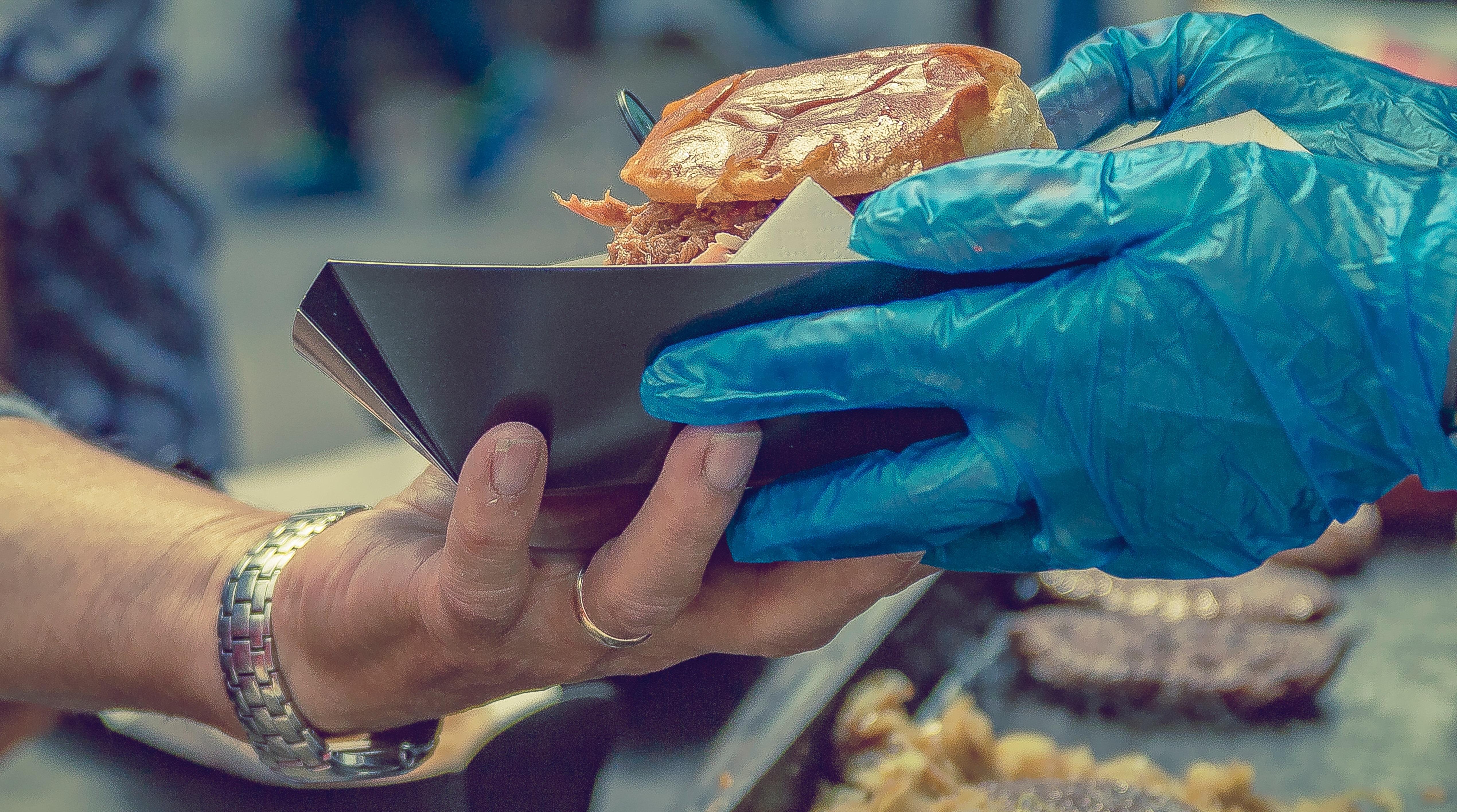 imagem de uma mão com luvas entregando um hambúrguer -  - ISO 22000 - Saúde e segurança de alimentos e Segurança Alimentar