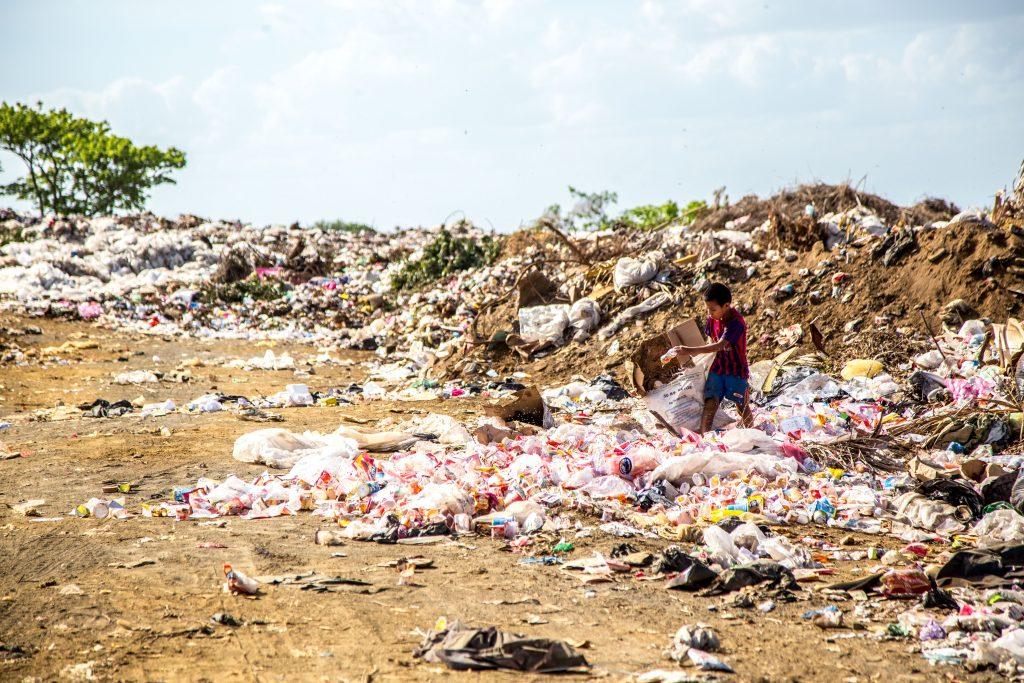 uma criança no meio de um amontoado de lixo buscando por caixas de papelão - coleta seletiva