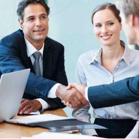 Como gerenciar os requisitos legais? - Pessoas reunidas em uma mesa, dando as mãos de modo a simbolizar o fechando novos negócios