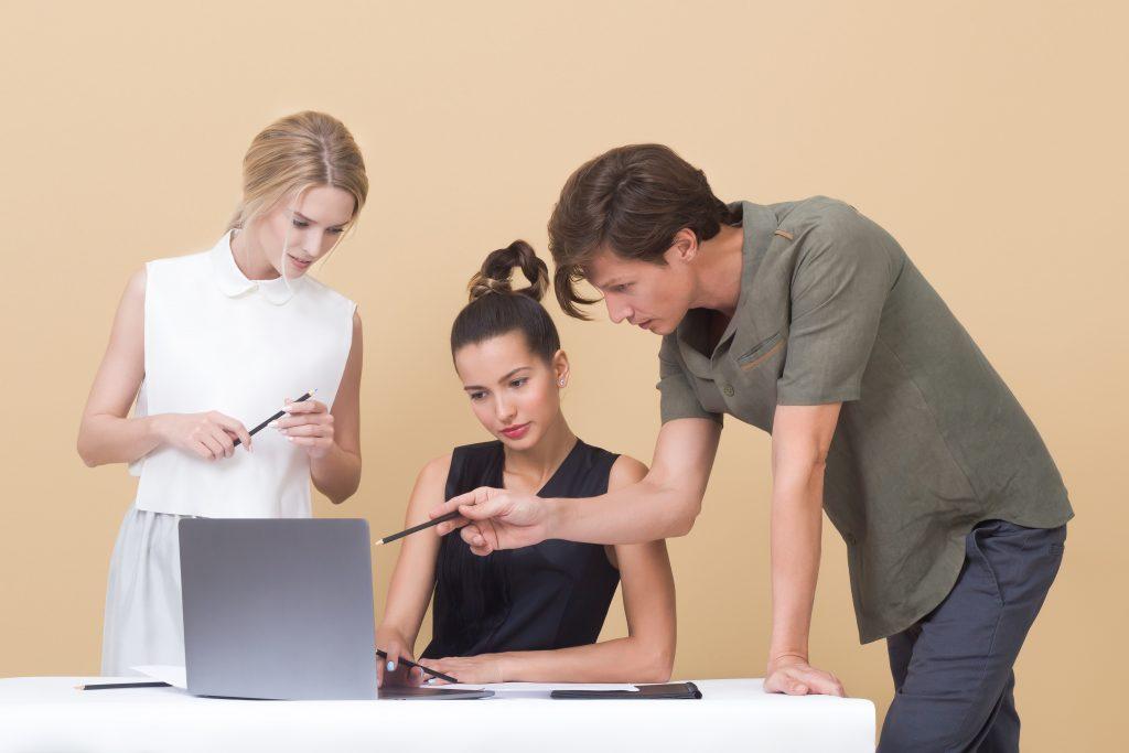 Duas mulheres e um homem discutindo sobre algo no computador. Gestão em SSO - Saúde e Segurança Ocupacional