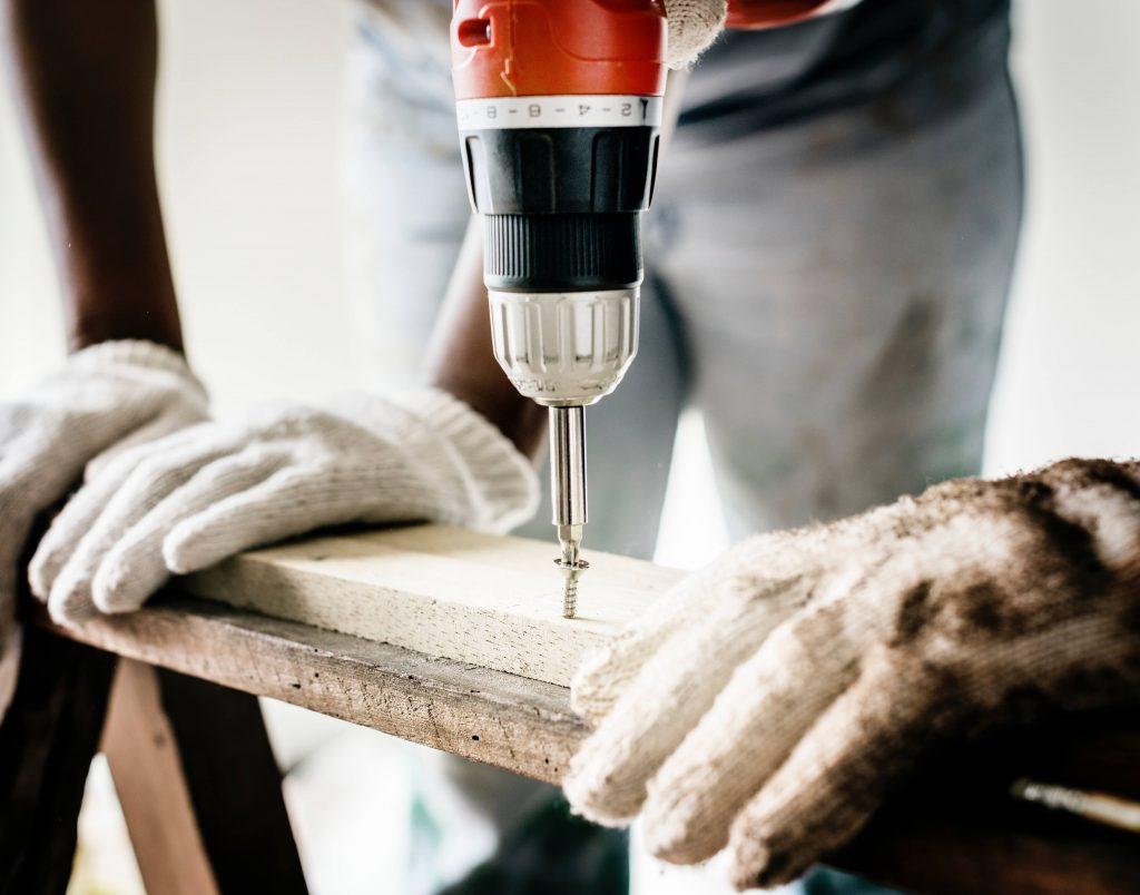 trabalhadores segurando tábuas e uma furadeira  - Gestão de Saúde e Segurança Ocupacional em atividades com inflamáveis e Líquidos Combustíveis – NR 20
