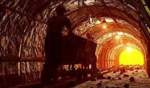 mina de minério com um homem empurrando o carrinho no trilho.