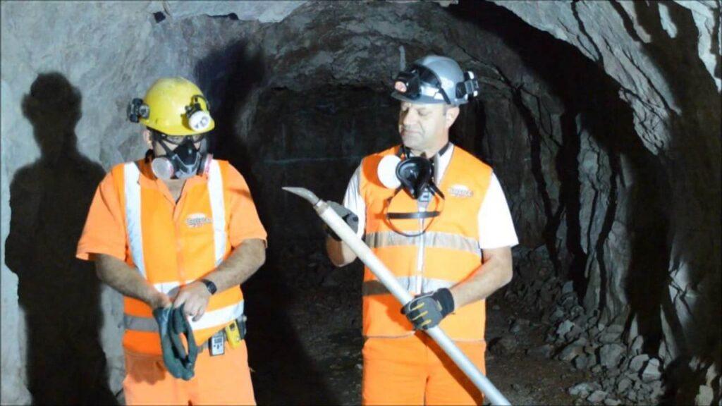 homem trabalhando com máscara de poeira em mina de minério de ferro.