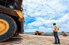 homem próximo a um trator, num ambiente de mineração. principais aspectos e regras de segurança ocupacional na mineração – NR 22