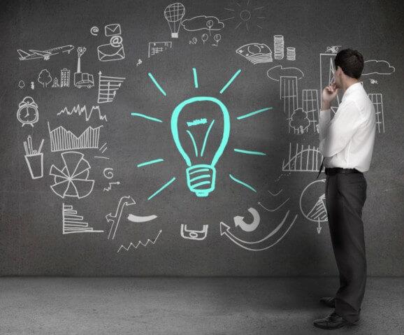 Homem olhando o desenho na parede feito de giz com vários símbolos relacionados à indústria e organizações e no meio uma lâmpada desenhada em giz verde - Coleta Seletiva nas Organizações