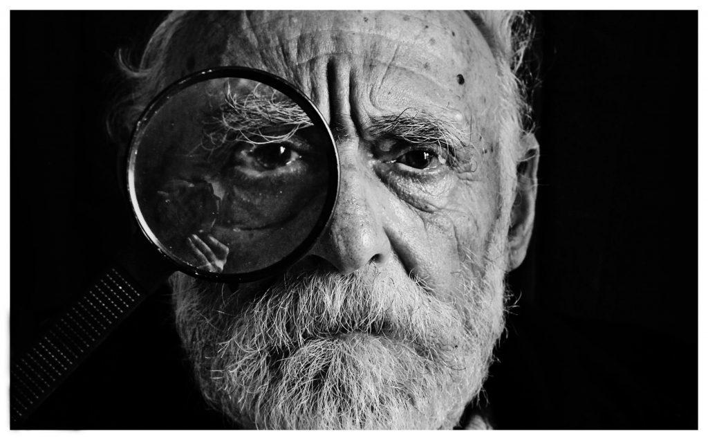 homem com mais de 60 anos com uma lupa em frente ao seu olho - Direito para aposentadoria especial
