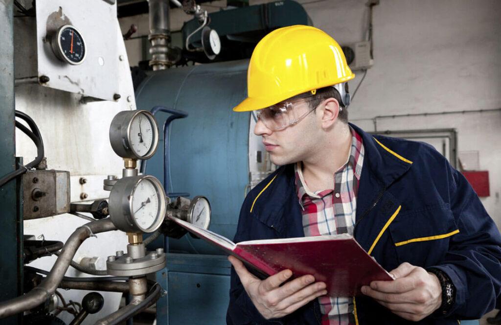 Homem fazendo gestão da segurança e da saúde - SSO - observando dados de pressurização da máquina - Nr 12