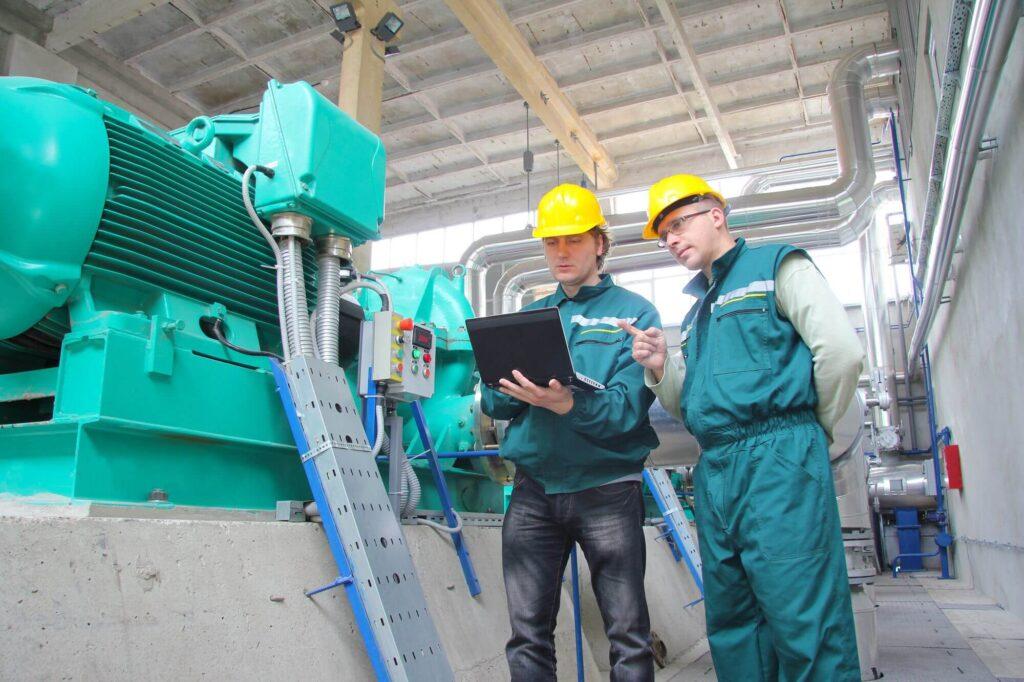 Homens na fábrica realizando manutenção dos equipamentos - O que é Gestão de Saúde e Segurança Ocupacional