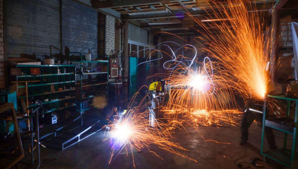 Homem trabalhando com solda e vários brilhos do ferro sendo soldado. Gestão em SSO