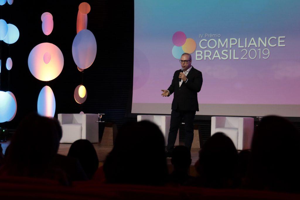 CEO Deivison Pedroza em um palco, explicando quais requisitos uma empresa deve cumprir para ser premiada no Prêmio Compliance.