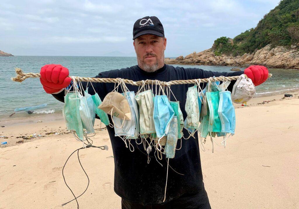Gary Stokes, fundador do grupo pela conservação marinha OceansAsia, mostra máscaras coletadas em praia de Hong Kong